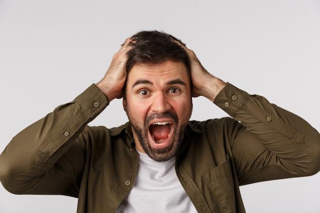 Man in paniek en angst zijn verstand kwijt te raken, van streek en gealarmeerd. onrustige verbaasde en depressieve knappe bebaarde man grijpt het hoofd en schreeuwt, kan geen problemen oplossen