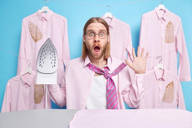 Man in paniek staart verrassend haastig en jurken voor werk ijzeren kleding poses in de buurt van strijkplank draagt overhemd met stropdas geïsoleerd op blauw