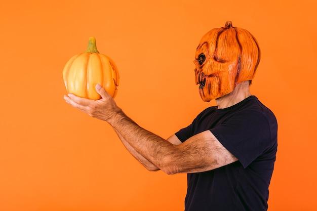 Man in profiel, met een angstaanjagend pompoenlatexmasker met een blauw t-shirt, houdt een 'jack-o-lantern'-pompoen vast en kijkt ernaar, op een oranje achtergrond. halloween en dagen van het dode concept.