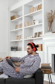 Man in pyjama met behulp van het zijaanzicht van de laptop