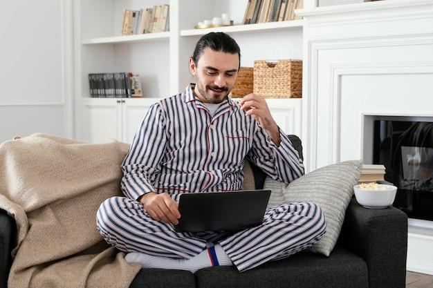 Man in pyjama's leuke tijd doorbrengen op laptop
