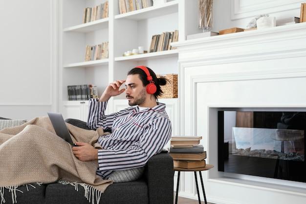 Man in pyjama's met behulp van de laptop binnenshuis