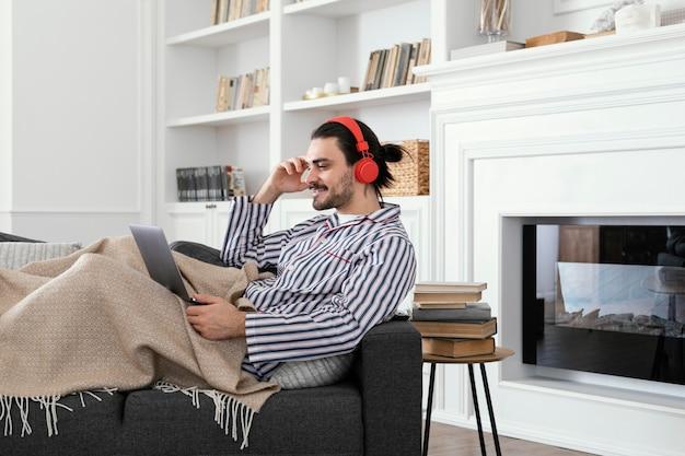 Man in pyjama's met behulp van de laptop