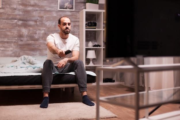 Man in pyjama 's nachts in bed kijken naar een film op grote tv.