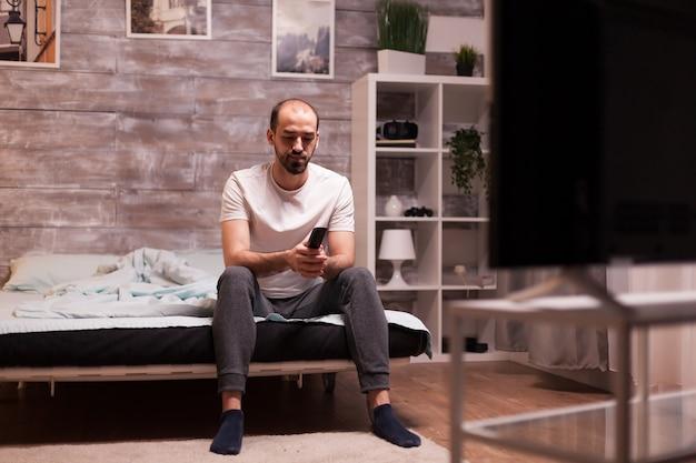 Man in pyjama 's nachts tv kijken met behulp van afstandsbediening.