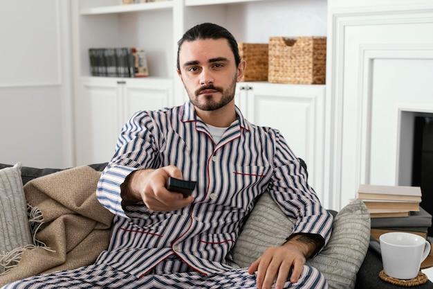 Man in pyjama's zijn tijd binnenshuis doorbrengen