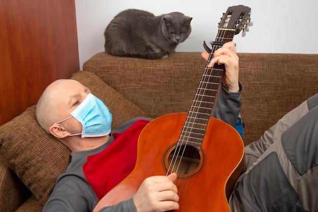 Man in quarantaine thuis met een medisch masker op zijn gezicht ligt op de bank en speelt gitaar. rust tijdens de coronavirusepidemie.