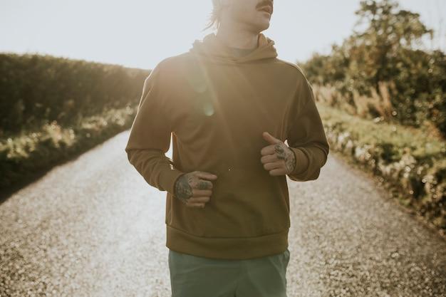 Man in rekbare hoodie joggen op het platteland bij zonsondergang