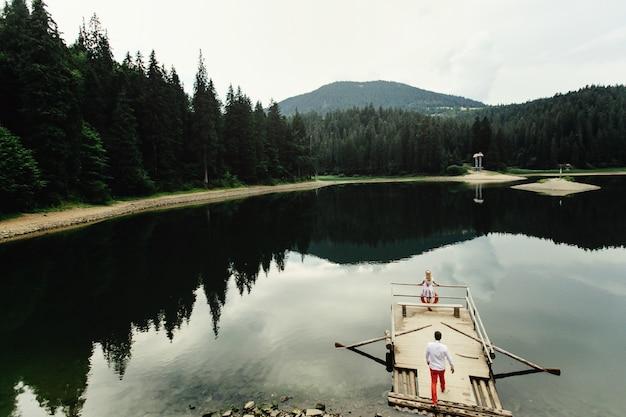 Man in rode broek loopt naar eenzame dame die op houten boot over bergmeer staat