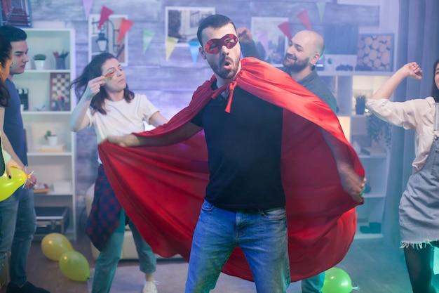 Man in rode cape van superheld dansen met zijn vrienden.