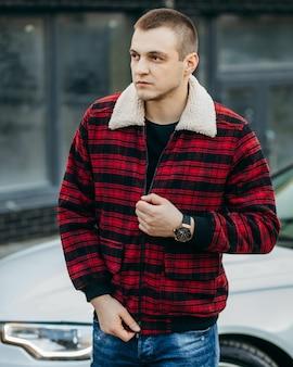 Man in rode geruite jas met witte luxeauto