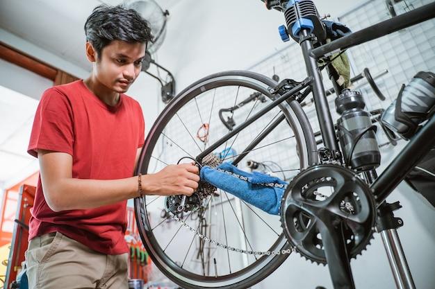 Man in rode kleren bezig met het repareren van een probleem van de fietsas met een moersleutel