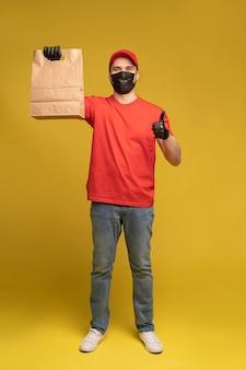 Man in rode pet, t-shirt in beschermend masker en handschoenen die fastfood bestellen geïsoleerd op gele muur