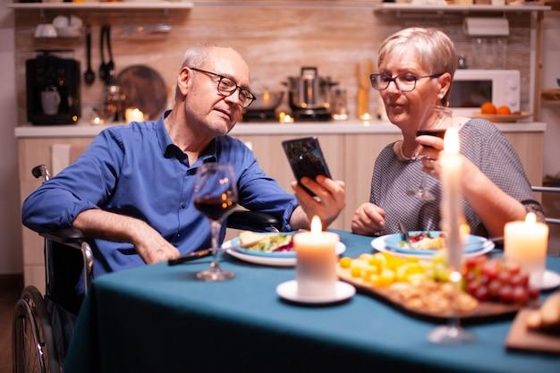 Man in rolstoel die telefoon vasthoudt terwijl hij dineert met zijn vrouw in de keuken. scrollen en foto's laten zien. geïmobiliseerde gehandicapte senior echtgenoot die telefoneert en geniet van de feestelijke maaltijd.