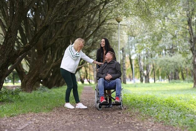 Man in rolstoel en lachende vriendinnen wandelen in park revalidatie van gehandicapten