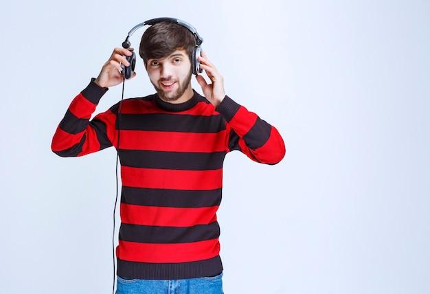 Man in rood gestreept shirt die de koptelefoon afdoet om uiterlijke stemmen te horen.