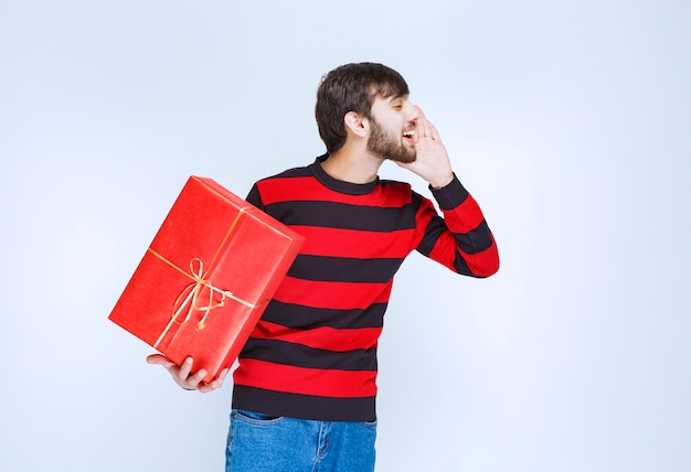 Man in rood gestreept shirt die een rode geschenkdoos vasthoudt en iemand roept om het te bezorgen.