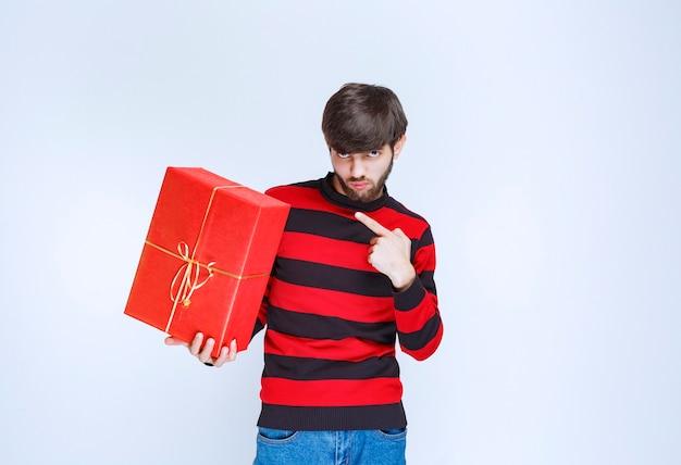 Man in rood gestreept shirt die een rode geschenkdoos vasthoudt en promoot.