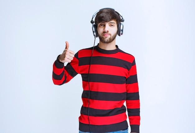 Man in rood gestreept shirt die naar een koptelefoon luistert en een teken van plezier toont.