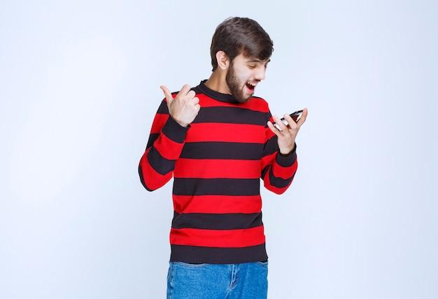 Man in rood gestreept shirt die telefoon vasthoudt en zijn selfie in energieke poses neemt.