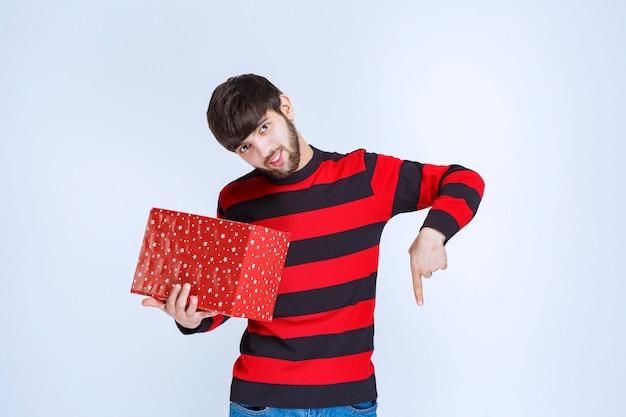 Man in rood gestreept shirt met een rode geschenkdoos en belt iemand om het te presenteren.
