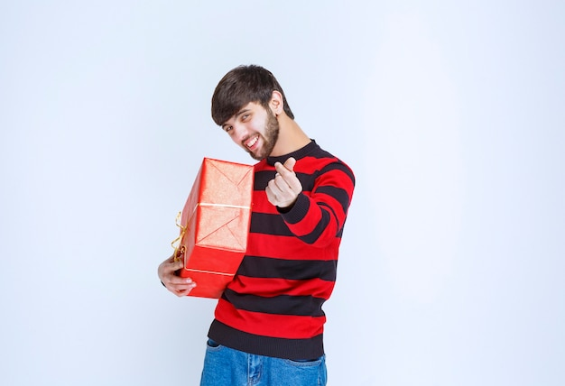 Man in rood gestreept shirt met een rode geschenkdoos en om betaling te vragen.