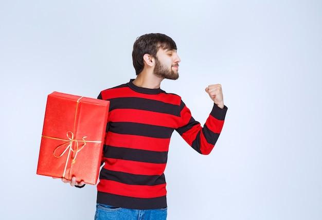 Man in rood gestreept shirt met een rode geschenkdoos en voelt zich krachtig en positief.