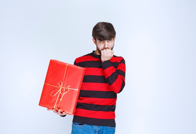 Man in rood gestreept shirt met een rode geschenkdoos en ziet er verward en attent uit.