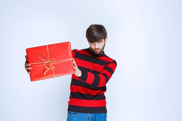 Man in rood gestreept shirt met een rode geschenkdoos, levert en presenteert deze aan de klant of aan zijn vriendin.