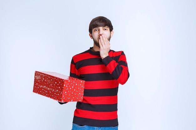 Man in rood gestreept shirt met een rode geschenkdoos ziet er bang en bang uit.