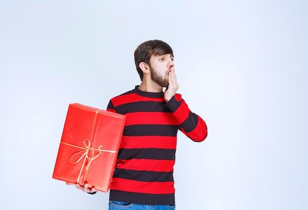 Man in rood gestreept shirt met een rode geschenkdoos ziet er moe en slaperig uit.