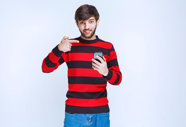 Man in rood gestreept shirt met een zwarte smartphone en erop wijzend.