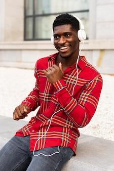 Man in rood shirt dansen en luisteren naar muziek