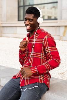Man in rood shirt dansen met zijn koptelefoon op