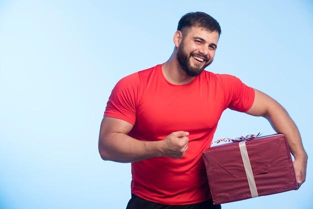 Man in rood shirt met een grote geschenkdoos en erop wijzend.