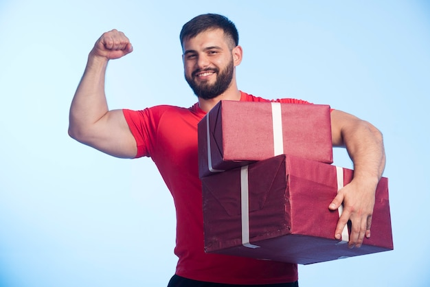 Man in rood shirt met een grote geschenkdoos en ziet er sterk uit
