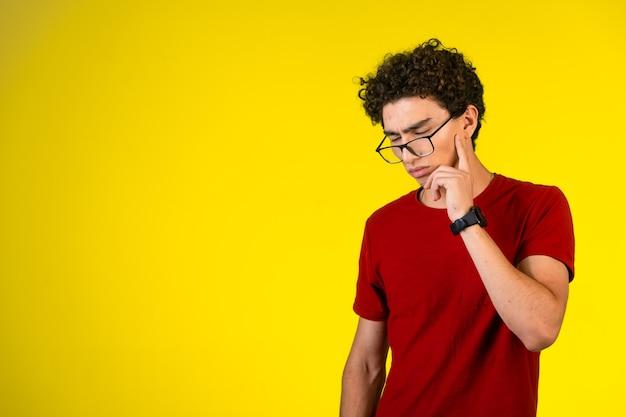 Man in rood shirt naar beneden te kijken en te denken
