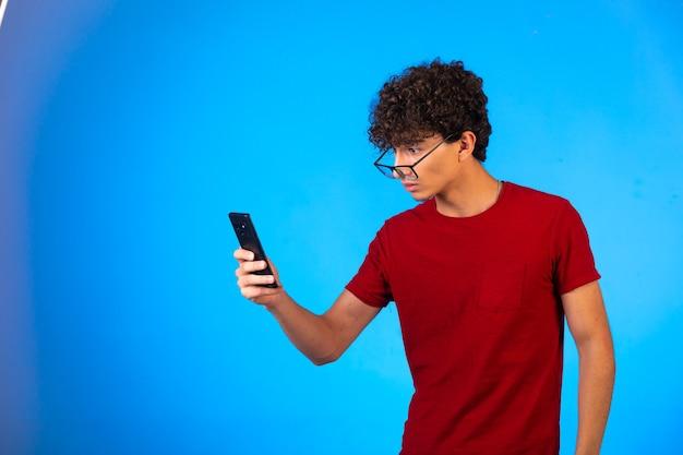 Man in rood shirt selfie te nemen of een telefoontje te plegen en kijkt boos