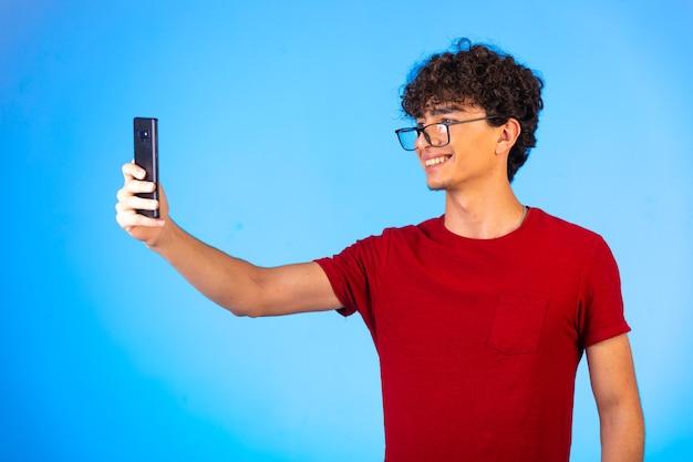 Man in rood shirt selfie te nemen of een telefoontje te plegen en plezier te hebben op blauw