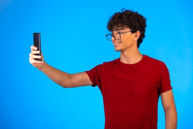 Man in rood shirt selfie te nemen of een telefoontje te plegen en plezier te hebben op blauwe achtergrond.
