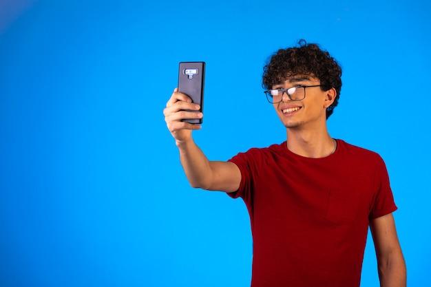 Man in rood shirt selfie te nemen of een telefoontje te plegen.