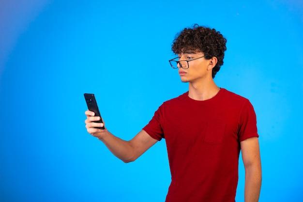 Man in rood shirt selfie te nemen of te bellen en kijkt verward.