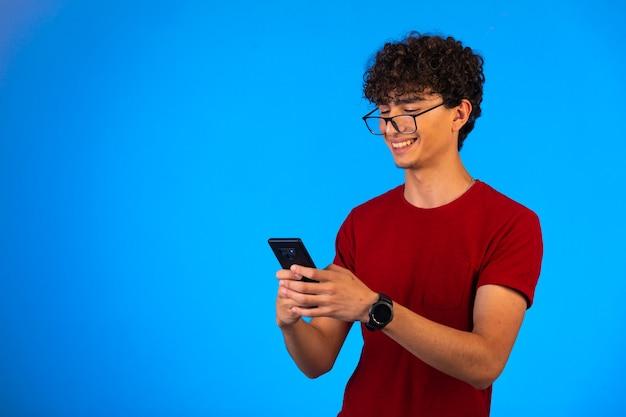 Man in rood shirt selfie te nemen op een smartphone op blauw en lachen.