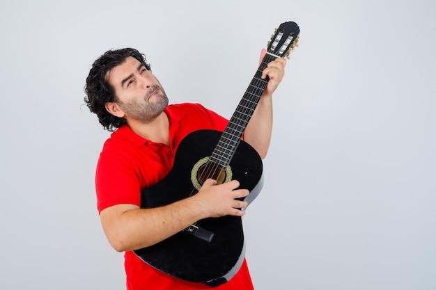 Man in rood t-shirt gitaar spelen en peinzend op zoek