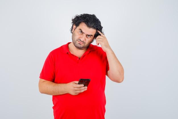 Man in rood t-shirt met telefoon, wijsvinger op tempel zetten en peinzend kijken.