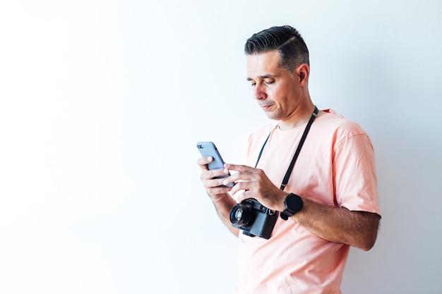 Man in roze t-shirt met een ouderwetse fotomachine over zijn schouder