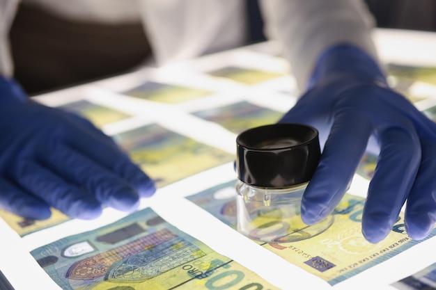Man in rubberen handschoenen die de echtheid van eurobiljetten controleert met behulp van vals geld van de lensclose-up