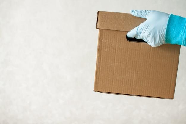 Man in rubberen handschoenen en een medisch masker levert kartonnen doos