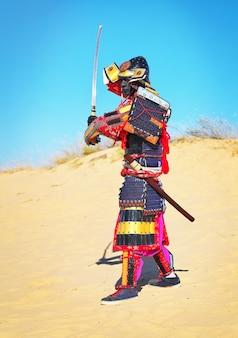 Man in samoeraikostuum met zwaard dat op het zand loopt. mannen in samoeraienpantser die op het zand rennen. origineel personage