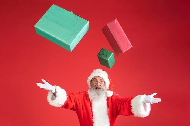 Man in santa kostuum geschenken in de lucht gooien